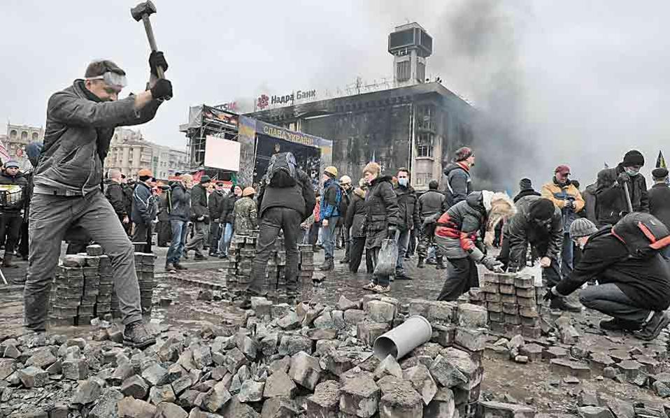 Διαδηλωτές διαλύουν σε κομμάτια τον λιθόστρωτο δρόμο και έπειτα τα εκσφενδονίζουν κατά των αστυνομικών δυνάμεων.