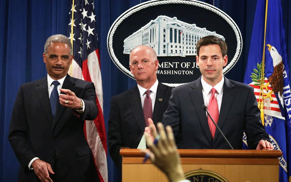 Ο Ερικ Χόλντερ, υπουργός Δικαιοσύνης των Ηνωμένων Πολιτειών (αριστερά) και άλλοι υψηλόβαθμοι αξιωματούχοι του υπουργείου Δικαιοσύνης ακούν με προσοχή τις ερωτήσεις των δημοσιογράφων και προσπαθούν να εξηγήσουν πώς οι Κινέζοι χάκερ υπέκλεπταν από τους αμερικανικούς επιχειρηματικούς κολοσσούς μυστικά, τα οποία θα μπορούσαν να φανούν ωφέλιμα στους Κινέζους ανταγωνιστές τους ή εξαπέλυαν κυβερνοεπιθέσεις.