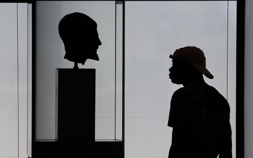 Τουρίστας θαυμάζει το ελληνικό κάλλος στο Μουσείο της Ακρόπολης, χωρίς να φαντάζεται, κατά πάσα πιθανότητα, τον νεοελληνικό κάλο ― στον εγκέφαλο...