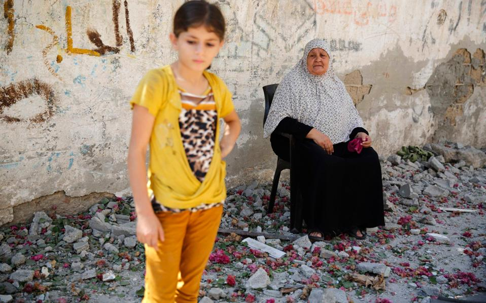 Ενα κορίτσι και μία γυναίκα στα συντρίμμια κατεστραμμένου από ισραηλινούς βομβαρδισμούς κτιρίου στον προσφυγικό καταυλισμό στη Γάζα.