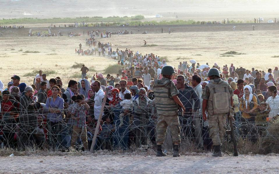 Τούρκοι στρατιώτες βλέπουν τις γραμμές των προσφύγων να πυκνώνουν πίσω από τον μεθοριακό φράχτη.