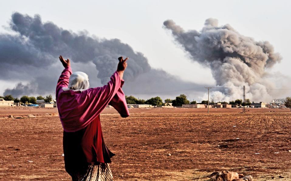 Πυκνοί καπνοί υψώνονται από την πολιορκούμενη κουρδική πόλη Κομπάνι, στα τουρκοσυριακά σύνορα, ύστερα από βομβαρδισμούς της αμερικανικής αεροπορίας κατά των τζιχαντιστών, τους οποίους επικροτεί με ενθουσιασμό Κούρδισσα από την άλλη πλευρά των συνόρων.