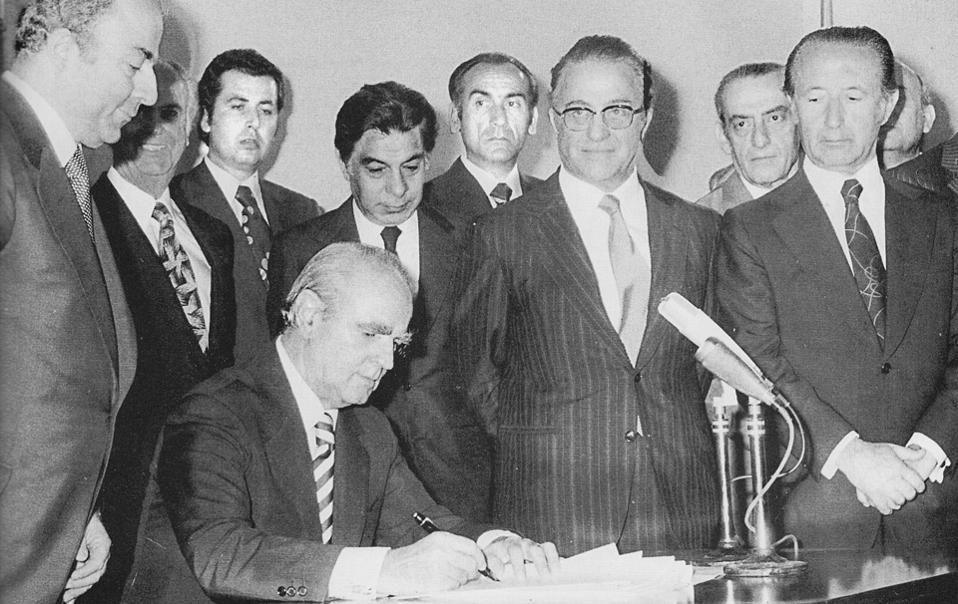 Ο Κωνσταντίνος Καραμανλής υπογράφει το νέο Σύνταγμα της χώρας στις 9 Ιουνίου 1975. «Ο Καραμανλής ήταν πεπεισμένος ότι ο Πρόεδρος της Δημοκρατίας, ως σύμβολο για τον λαό, θα πρέπει να εκλέγεται με τη στήριξη ευρύτερων πολιτικών δυνάμεων και όχι αποκλειστικά από την εκάστοτε κυβερνητική παράταξη», τονίζει στην «Κ» ο πρώην υπουργός και μέλος της τότε συντακτικής επιτροπής του Συντάγματος Ιωάννης Βαρβιτσιώτης.