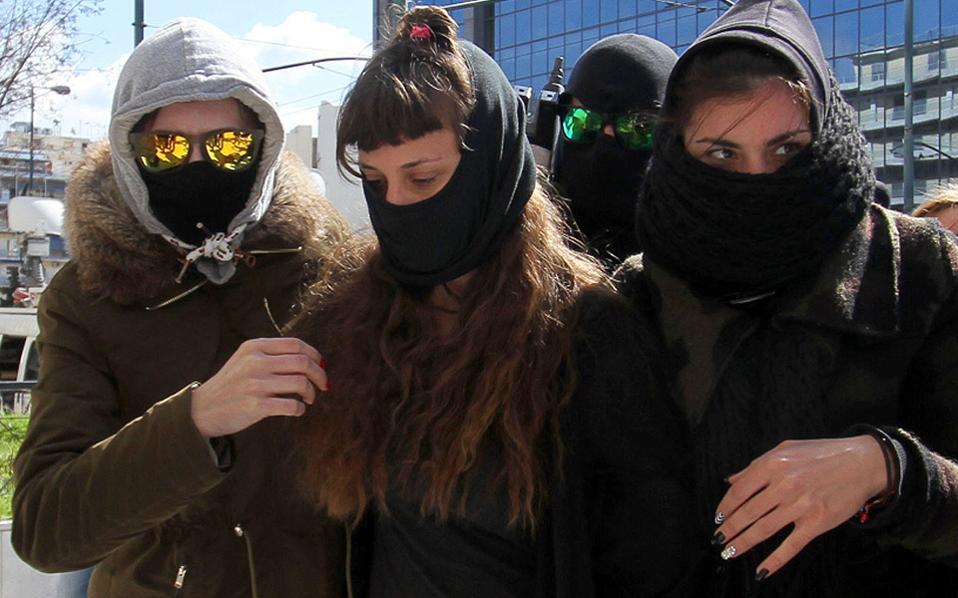 Η σύντροφος του καταδικασμένου για συμμετοχή στην οργάνωση «Συνωμοσία Πυρήνων της Φωτιάς», Γεράσιμου Τσάκαλου, στο μέσον μεταξύ δύο αστυνομικών, οδηγείται στην Αντιτρομοκρατική Υπηρεσία, μετά τη σύλληψή της χθες στη Σαλαμίνα.