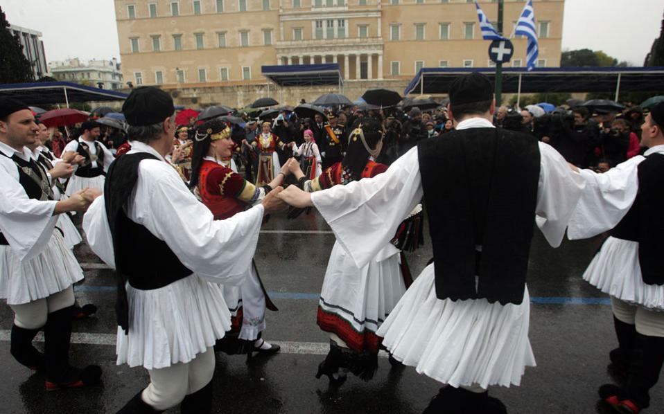 Mέλη πολιτιστικών συλλόγων, με παραδοσιακές στολές, χορεύουν υπό βροχή στην πλατεία Συντάγματος.