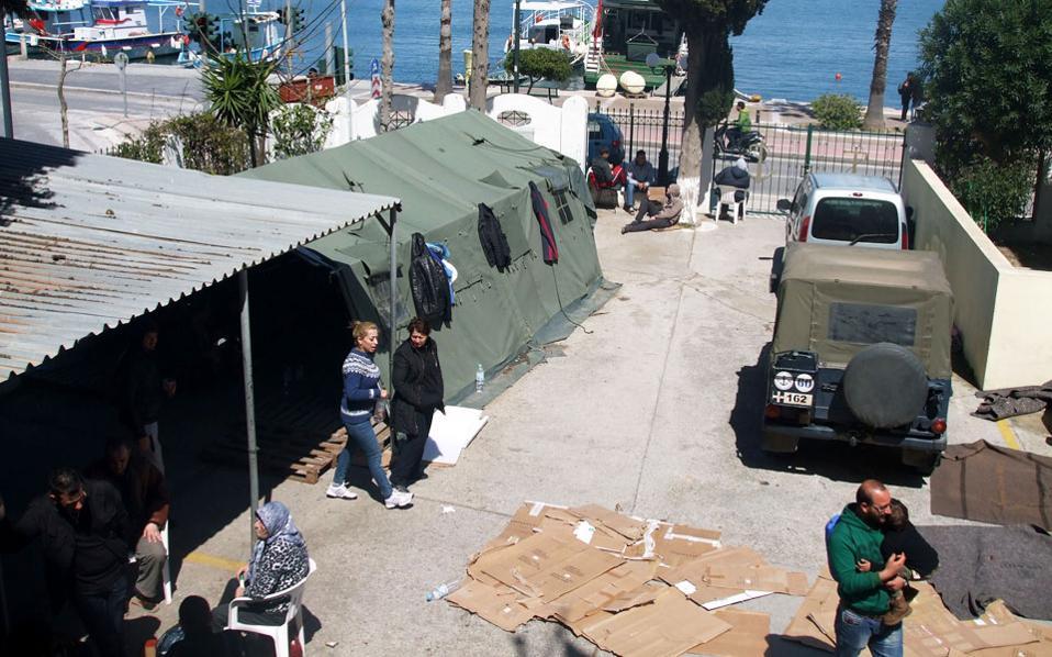 Μετανάστες στην αυλή του Λιμεναρχείου της Κω περιμένουν να λάβουν τη βεβαίωση εξάμηνης παραμονής στη χώρα και να πάρουν το πλοίο για τον Πειραιά. Δεν υπάρχουν υποδομές για να φιλοξενηθούν και καταλύουν πρόχειρα στο Λιμεναρχείο και στο αστυνομικό τμήμα.