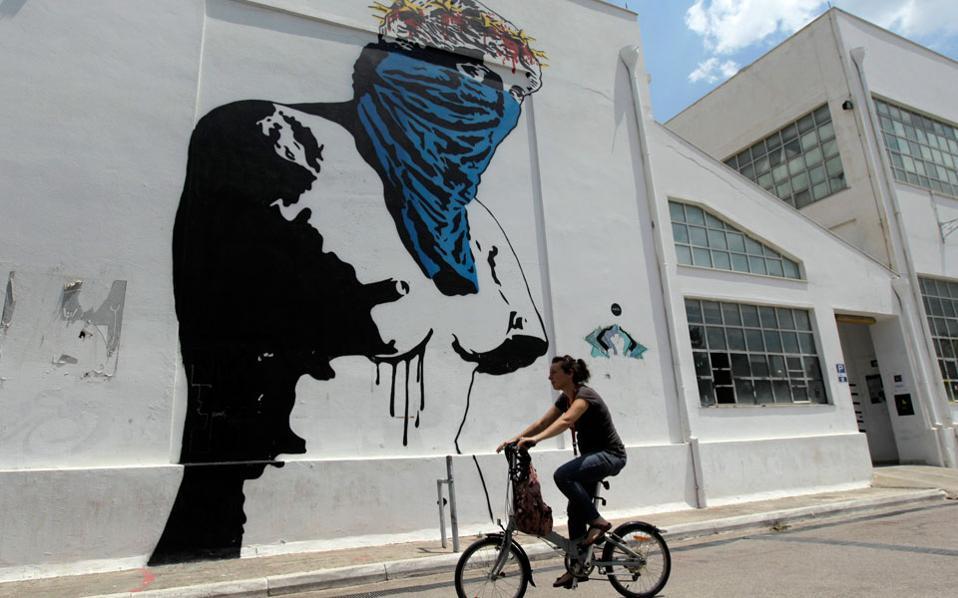 Αθήνα 2015: μία γυναίκα περνά με το ποδήλατό της μπροστά από γκράφιτι που απεικονίζει την Αφροδίτη της Μήλου με μαντίλι.