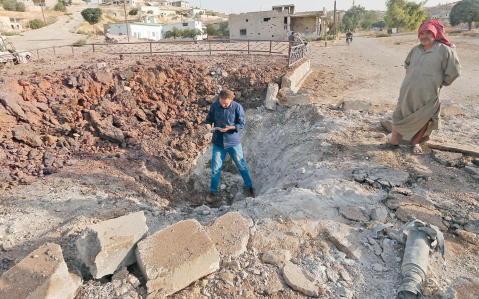 Πολίτες της Λατανμέχ, στα περίχωρα της συριακής πόλης Χάμα, επιθεωρούν τον κρατήρα που άνοιξε βόμβα ρωσικού, μαχητικού αεροσκάφους. Ο διοικητής μονάδων της φιλοδυτικής αντιπολίτευσης στην περιοχή κατήγγειλε ότι οι ρωσικοί βομβαρδισμοί τραυμάτισαν οκτώ άνδρες του.