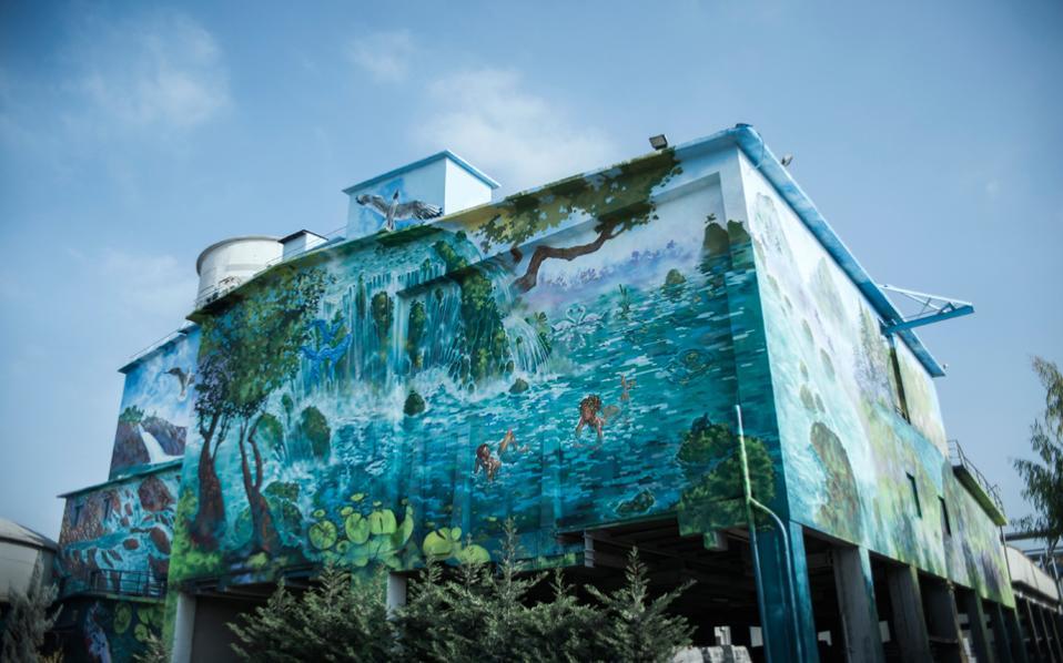 Με ιμπρεσιονιστικό πίνακα μοιάζει το εντυπωσιακό έργο- γκράφιτι που εδώ και λίγες μέρες καλύπτει τους τοίχους της τσιμεντοβιομηχανίας ΤΙΤΑΝ στην Ευκαρπία Θεσσαλονίκης. Για το έργο, που καλύπτει συνολικά 2.000 τετραγωνικά μέτρα βιο- μηχανικής επιφάνειας, χρειάστηκε ένας χρόνος δουλειάς σε δέκα στάδια, 120 κιλά ακρυλικού χρώματος, 5.000 κουτιά σπρέι. Το υπογράφουν οι Θεσσαλονικείς Βασίλης και Χρήστος Γαλαζούλας της εταιρείας graffiti and design MWCOE.
