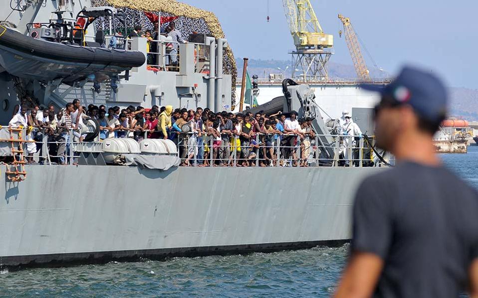 Ανδρας της ιταλικής ακτοφυλακής επιβλέπει αποβίβαση μεταναστών.