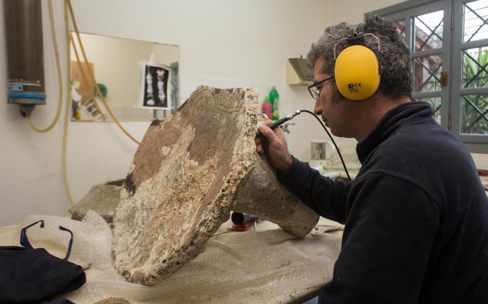 Ο Αγγελος Τσομπανίδης εργάζεται πάνω σε ένα αντικείμενο που μοιάζει (και μπορεί να είναι) με μικρό τραπέζι και βρέθηκε στους Φούρνους.