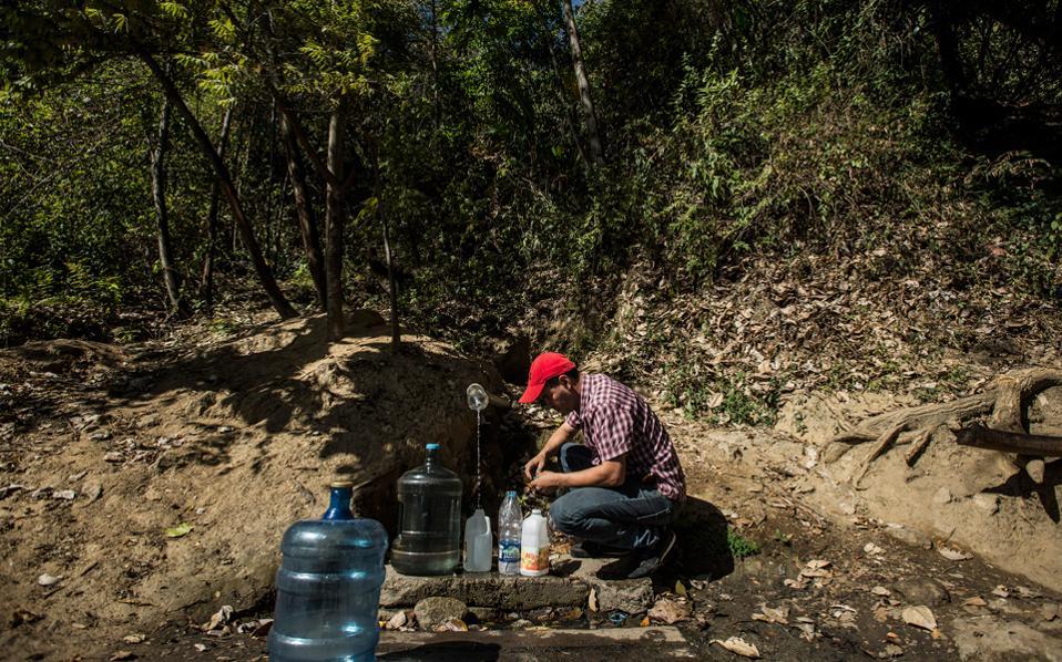 Στη Βενεζουέλα το νερό είναι ελάχιστο και πανάκριβο. Oι κάτοικοι περιμένουν να γεμίσουν τις φιάλες τους από μια πηγή που ίσα ίσα τρέχει στην πλαγιά ενός βουνού.