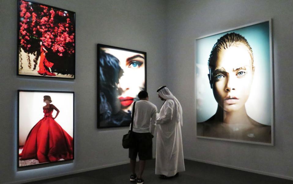 b8f9d460d1f Φωτογραφική εμπειρία στο Dubai. Επισκέπτες κοιτούν τον κατάλογο της έκθεσης  «Heat» του Περουβιανού φωτογράφου μόδας Mario Testino.