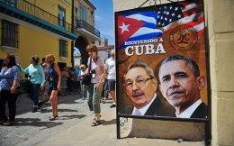 Τουρίστες περπατούν δίπλα από αφίσα του Κουβανού προέδρου Ραούλ Κάστρο και του Αμερικανού προέδρου Μπαράκ Ομπάμα στην Αβάνα.