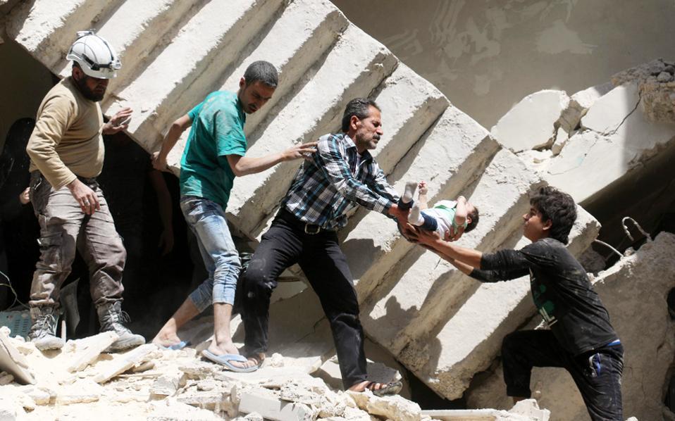 Στη φωτογραφία, άνδρες σωστικού συνεργείου και εθελοντές απομακρύνουν βρέφος από τα συντρίμμια βομβαρδισμένου κτιρίου σε περιοχή του Χαλεπίου που ελέγχεται από αντικαθεστωτικούς.