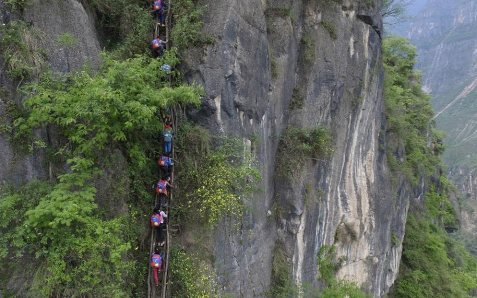 Στον δρόμο για το σχολείο. Έναν γκρεμό 800 μέτρων πρέπει να διαβούν  τα παιδιά της Zhaoiue της επαρχίας Sichuan στην Κίνα, για να πάνε στο σχολείο τους. Και το κάνουν καθημερινά, με τις σάκες στους ώμους για να είναι τα χέρια ελεύθερα για το σκαρφάλωμα. Ελπίζουν δε σε καλύτερες μέρες, καθώς η σκάλα από μπαμπού που τους βοηθά στην αναρρίχηση καθημερινά, θα αντικατασταθεί με  μια από ατσάλι. Chinatopix via AP