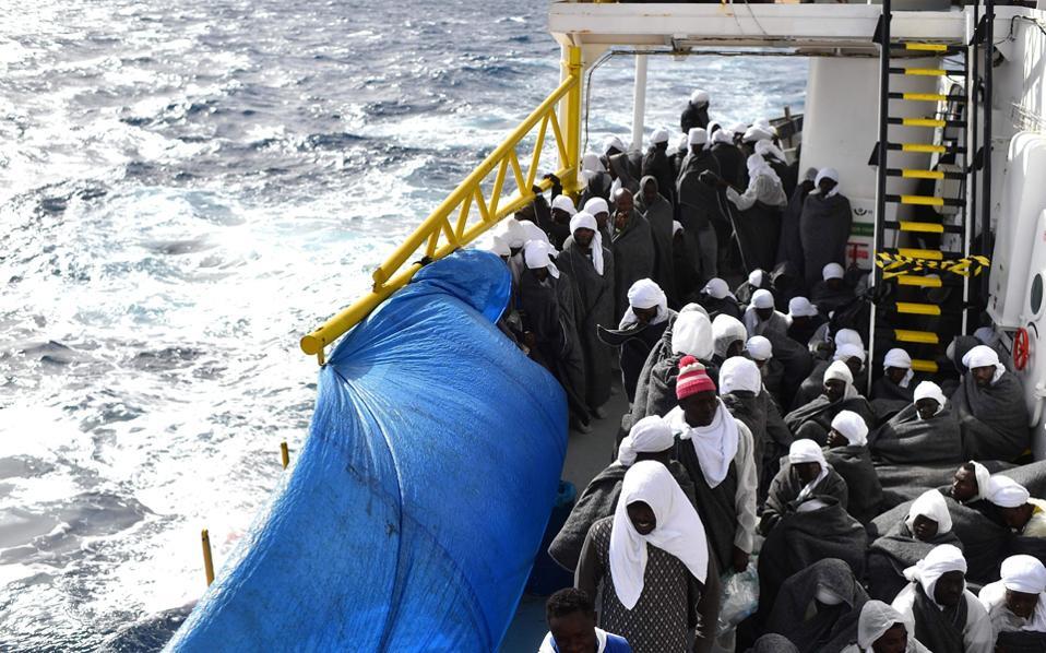 Μετανάστες προσπαθούν να προστατευθούν από το κρύο με κουβέρτες, καθώς καταφθάνουν στη Σαρδηνία.