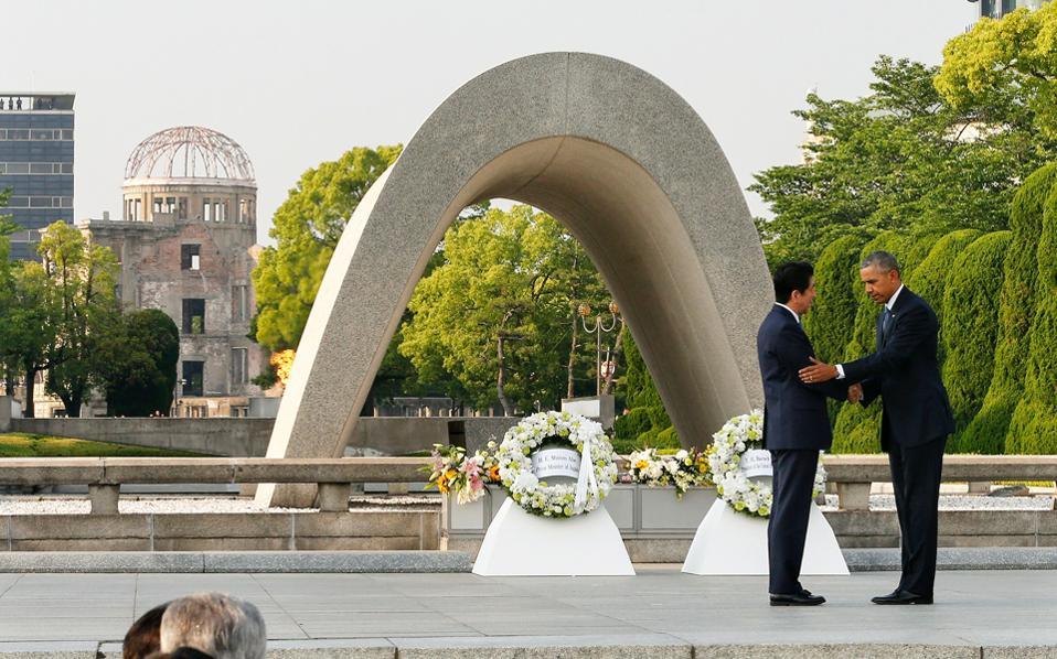 Φόρο τιμής στα θύματα της αμερικανικής ατομικής βόμβας απέτισε χθες ο Μπαράκ Ομπάμα, ο πρώτος εν ενεργεία πρόεδρος των ΗΠΑ που επισκέφθηκε τη Χιροσίμα. Στη φωτογραφία, ο Αμερικανός πρόεδρος ανταλλάσσει χειραψία με τον Ιάπωνα πρωθυπουργό, Σίνζο Αμπε, στο κενοτάφιο της μαρτυρικής πόλης.