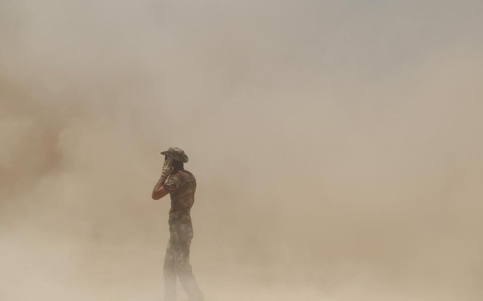 Ενοπλος καλύπτει τα αυτιά του εν μέσω βολών πυροβολικού εναντίον του Ι.Κ., κοντά στη Φαλούτζα.
