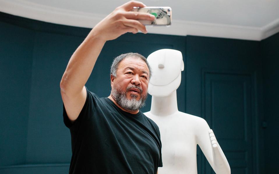 Ο Αϊ Ουέι Ουέι αυτοφωτογραφίζεται στο Μουσείο Κυκλαδικής Τέχνης μπροστά από την Ιστάμενη Μορφή, έργο που παρουσιάζεται στην έκθεση.