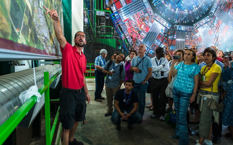 Εκπαιδευτικοί ξεναγούνται στις εγκαταστάσεις του πειράματος CMS σε παλαιότερο εκπαιδευτικό πρόγραμμα του CERN. Στην αεροφωτογραφία, δεξιά, διακρίνεται ο Μεγάλος Επιταχυντής Αδρονίων (LHC).