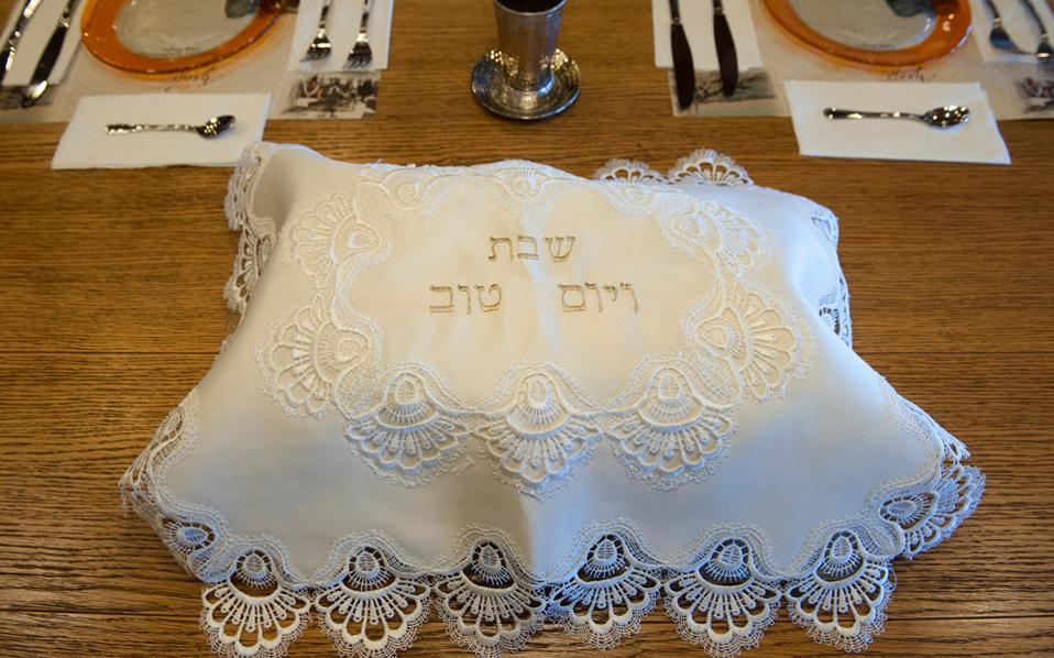 Το πανέρι με τα παραδοσιακά ψωμάκια χαλότ, σκεπασμένα με τον χρυσοκέντητο χαιρετισμό του Σαββάτου «Σαμπάτ Σαλόμ» (Σάββατο με ειρήνη).