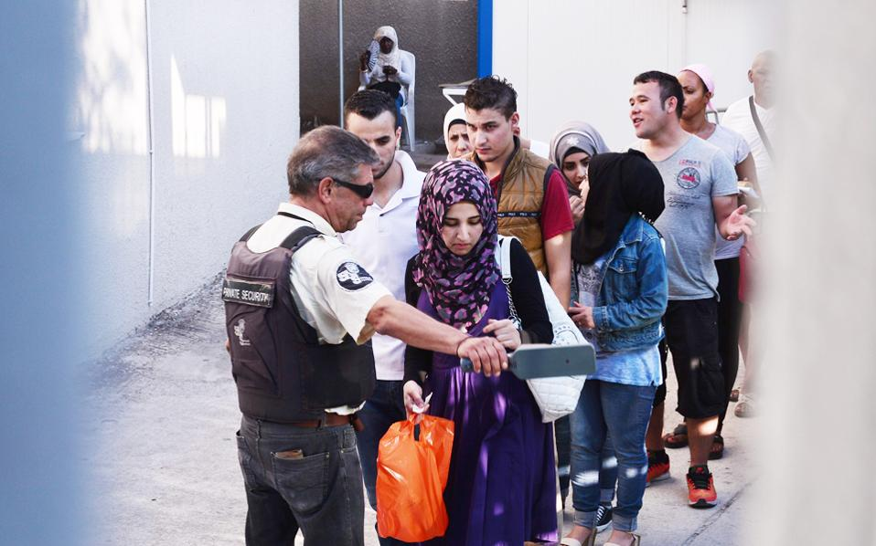 Στην ουρά πρόσφυγες και μετανάστες ελέγχονται από υπάλληλο για το αν φέρουν πάνω τους μεταλλικά αντικείμενα.