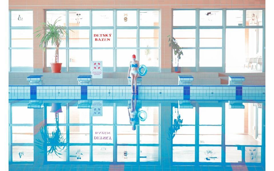 Το νερό, ολοκάθαρο και ακίνητο, στιλπνός καθρέφτης χωρίζει την εικόνα στα δύο και πολλαπλασιάζει υπόκωφα το τοπίο «ΚΟΛΥΜΠΗΣΕ», «SWIMM»,  © Photo, Art Direction: Maria Svarbova / Costume, Styling: Zuzana Hudakova, Martina Siranova