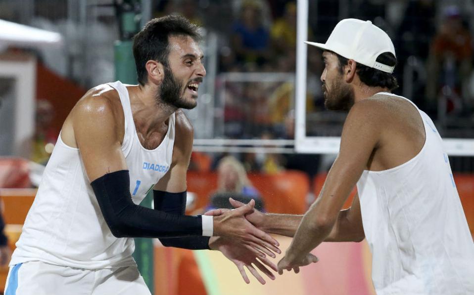 Και εσείς εδώ; Ο Paolo Nicolai και ο  Daniele Lupo της Ιταλίας αλληλοσυγχαίρονται για το παιχνίδι τους εναντίον της Ρωσίας στο μπιτς βολει.  REUTERS/Adrees Latif
