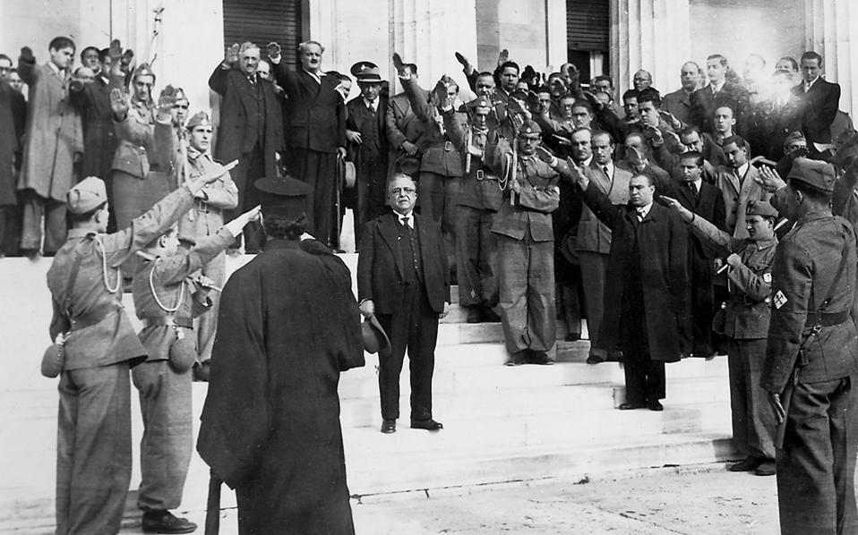 Ο Ιωάννης Μεταξάς, κατά τη διάρκεια εκδήλωσης των Ταγμάτων Εργασίας. Στην κορυφή της σκάλας, ο Κώστας Κοτζιάς –ασκεπής, με το καπέλο στο αριστερό χέρι– υπουργός Διοικήσεως Πρωτευούσης. Στο ίδιο σκαλοπάτι με τον κυβερνήτη, δεξιότερα, ο γενικός διευθυντής Γραμμάτων και Τεχνών του καθεστώτος Κωστής Μπαστιάς.