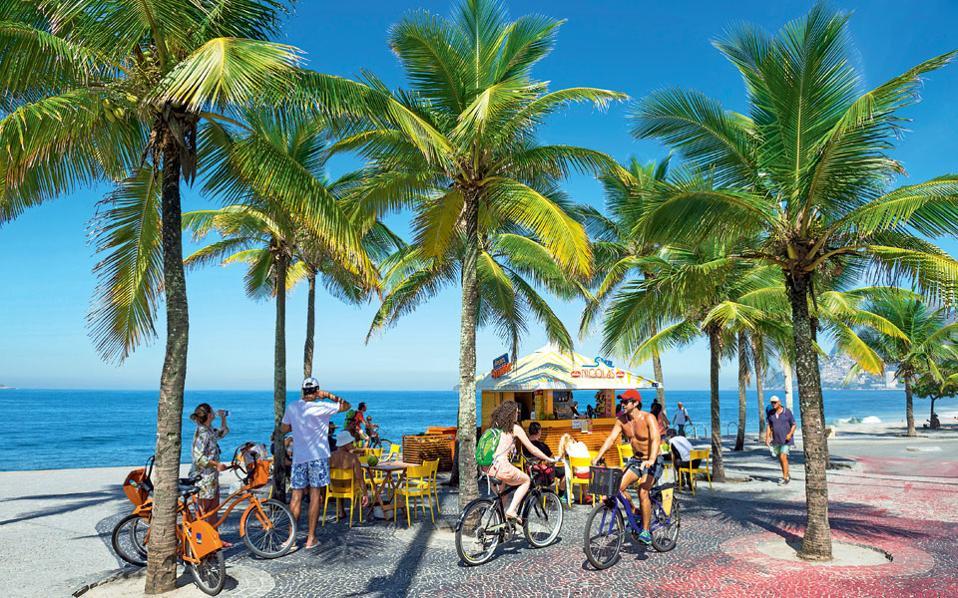 Ποδηλάτες κάνουν στάση για να αγοράσουν καρύδες, νερό κ.ά. από το κιόσκι στην Arpoador. (Φωτογραφία: Shutterstock)