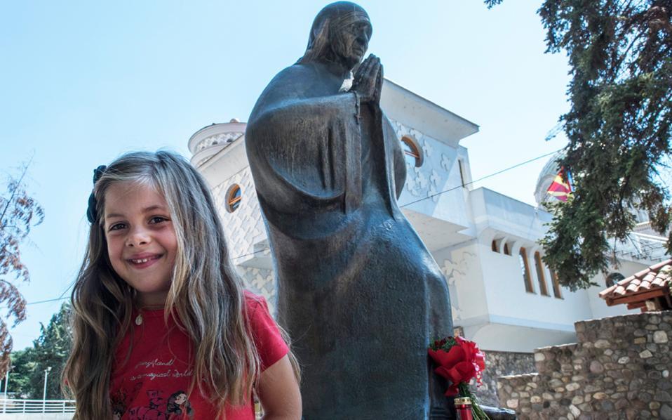 Η μικρή Αγνή Γκόντσε Βούκοβιτς, που ονομάσθηκε έτσι προς τιμήν της Μητέρας Τερέζας, στέκεται μπροστά σε άγαλμα της Αγίας στα Σκόπια.
