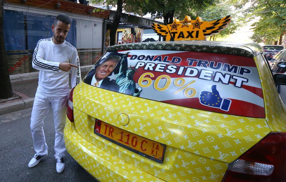Ένας Αλβανός στο πλευρό του Donald Trump. Στην διατύπωση του πρωθυπουργού Edi Rama ότι μια «εκλογή του Trump θα είναι πραγματική απειλή για τις αλβανο-αμερικανικές σχέσεις» αντέδρασε ο ταξιτζής Uljan Kolgjegja, ετών 37. Μετά από αυτό το γεγονός, έκανε όλο το εσωτερικό του ταξί του στα χρώματα της αστερόεσσας, έβαλε στα τζάμια την φωτογραφία του αγαπημένου του υποψηφίου και είδε τις δουλειές στο κέντρο των Τιράνων να εκτοξεύονται. Το λογότυπο του Louis Vuitton σε κίτρινο που καλύπτει όλο το όχημα, είναι αυτό που πραγματικά απογειώνει την αισθητική της όλης δημιουργίας.(AP Photo/Hektor Pustina)