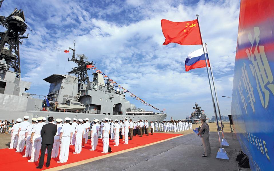 Αξιωματικοί και ναύτες του κινεζικού Πολεμικού Ναυτικού καλωσορίζουν τα ρωσικά πλοία που έφτασαν στο λιμάνι του Ζαντζιάνγκ για να πάρουν μέρος στα κοινά γυμνάσια των δύο χωρών, στα ταραγμένα νερά της Νότιας Σινικής Θάλασσας. Οι οκταήμερες ασκήσεις με πραγματικά πυρά περιλαμβάνουν εικονική ανακατάληψη νήσου από «εχθρικές δυνάμεις» και σηματοδοτούν την ενίσχυση της πολιτικής και στρατιωτικής συνεργασίας ανάμεσα στις δύο μεγάλες δυνάμεις της Ευρασίας. Σύμφωνα με όλες τις ενδείξεις, πάντως, οι ασκήσεις δεν θα λάβουν μέρος σε διαφιλονικούμενες περιοχές της Νότιας Σινικής Θάλασσας.
