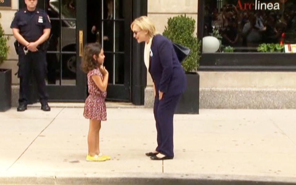 Η Χ. Κλίντον συνομιλεί με ένα κοριτσάκι έξω από το σπίτι της κόρης της, όπου αναπαύθηκε την Κυριακή, αφού ένιωσε αδιαθεσία στην τελετή για τα 15 χρόνια από τις επιθέσεις της 11ης Σεπτεμβρίου.