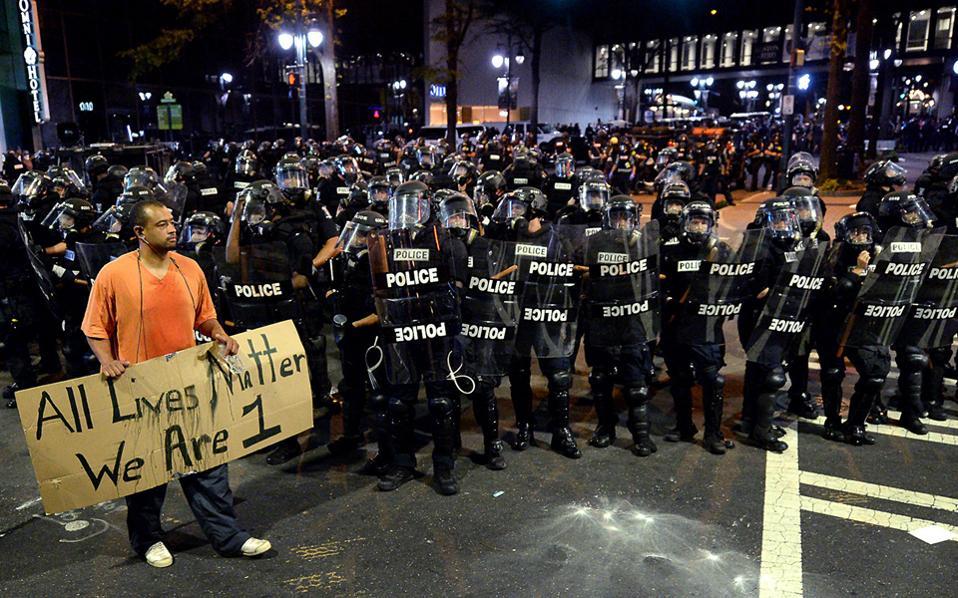Μήνυμα ανθρωπισμού και ενότητας δίνει αυτός ο διαδηλωτής στη Σάρλοτ της Βόρειας Καρολίνας με το πανό που γράφει: «Ολες οι ζωές είναι σημαντικές. Είμαστε ένα». Σε κατάσταση έκτακτης ανάγκης κήρυξε χθες τη Σάρλοτ ο κυβερνήτης της πολιτείας, ύστερα από δύο νύχτες ταραχών που ξέσπασαν μετά τη δολοφονία 43χρονου Αφροαμερικανού από αστυνομικό. Διαδηλωτές έσπασαν βιτρίνες και λεηλάτησαν εμπορικά καταστήματα, με την αστυνομία να απαντά με ρίψεις δακρυγόνων.