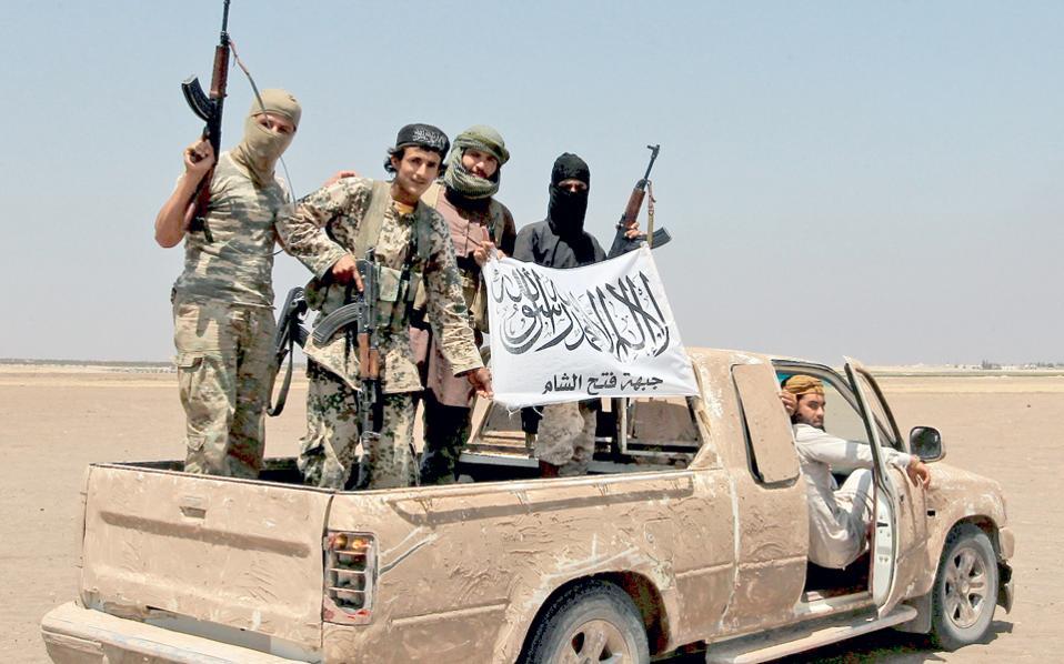Ενοπλοι της ισλαμικής αντικαθεστωτικής οργάνωσης Τζαμπάτ Φατάχ αλ Σαμ πανηγυρίζουν την κατάρριψη ρωσικού ελικοπτέρου στην επαρχία Ιντλίμπ, στη βορειοδυτική Συρία.