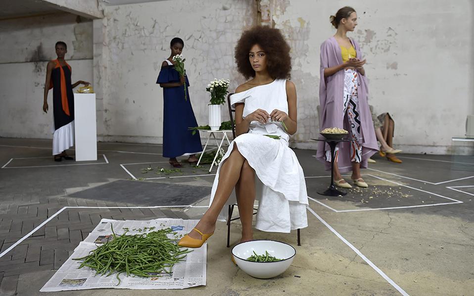 Φασολάκια και μυθοπλασία. Νότες καθημερινότητας θέλησε να δώσει στην παρουσίαση των μοντέλων της η Isa Arfen στο πλαίσιο Εβδομάδας Μόδας του Λονδίνου, με τα κορίτσια  να τοποθετούν λουλούδια στα βάζα ή να τσιμπολογούν ξηρούς καρπούς. Όσο για το κεντρικό μοντέλο, κάτι είναι λάθος, καθώς δεν υπάρχει γυναίκα που να έχει τα χρήματα να αγοράσει υψηλή ραπτική και να καθαρίζει φασολάκια. EPA/HANNAH MCKAY