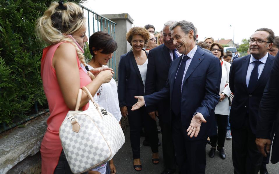 Αχου το! Ροζ φόρεμα, κλάμερ στο μαλλί, σινιέ τσάντα και το κινητό κολλημένο στο αυτί. Ο Nicola Sarkozy προσπαθεί να προσεγγίσει τις λαχτάρες της μεσαίας τάξης έξω από σχολείο στο Orgeval του Παρισιού στην διάρκεια προεκλογικής εκστρατείας του. AFP / POOL / PATRICK KOVARIK