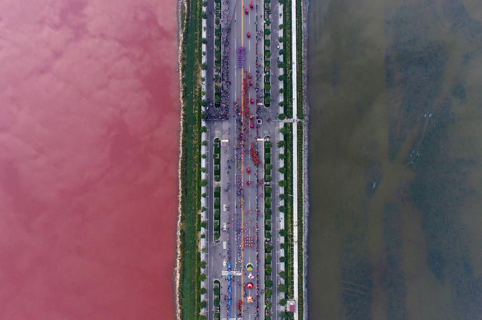 Μια λωρίδα για την μόλυνση. Τα νερά στην  αλμυρή λίμνη στην  Yuncheng της επαρχίας Shanxi χωρίζονται   στα δύο από μια γέφυρα. Αυτή είναι και ο λόγος που φαίνεται η ρύπανση της λίμνης διά γυμνού οφθαλμού και με διαφορετικό τρόπο. Κόκκινο από την μία, πηχτό πράσινο από την άλλη από την ανάπτυξη φυκών. REUTERS/Wei Liang