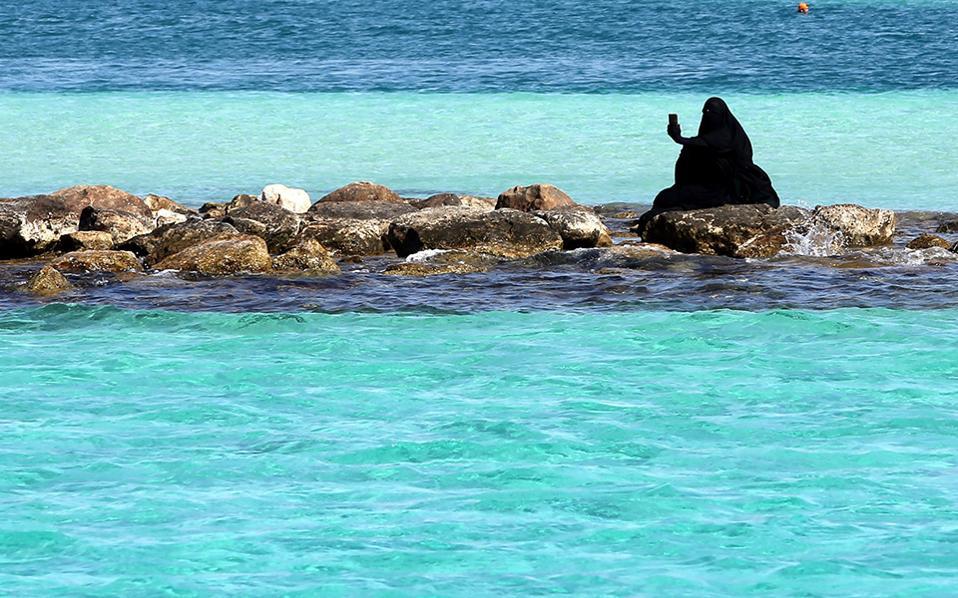 Μαγιό. Με το θερμόμετρο να έχει σκαρφαλώσει στους 40 βαθμούς Κελσίου, μια Αιγύπτια που φορά niqab (Ολη καλυμμένη, με γάντια στα χέρια και μια μικρή σχισμή στα μάτια) βγάζει selfie για να δείξει σε όλους το ειδυλλιακό γαλάζιο της   Marsa Matruh. EPA/KHALED ELFIQI
