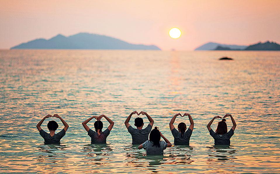 Tουρίστες παίζουν θαυμάζοντας το ηλιοβασίλεμα στη Sunset Beach του Ko Lipe. (Φωτογραφία: FRANCOIS FOURRIER)