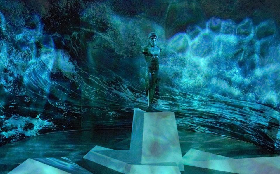 Το άγαλμα του θεού Ποσειδώνα και πίσω του η εικόνα της αγριεμένης θάλασσας είναι από τις εντυπωσιακότερες στιγμές της έκθεσης, η οποία πραγματοποιείται με τη βοήθεια του Ιδρύματος Στ. Νιάρχος. (Φωτογραφία: Ελευθέριος Γαλανόπουλος)