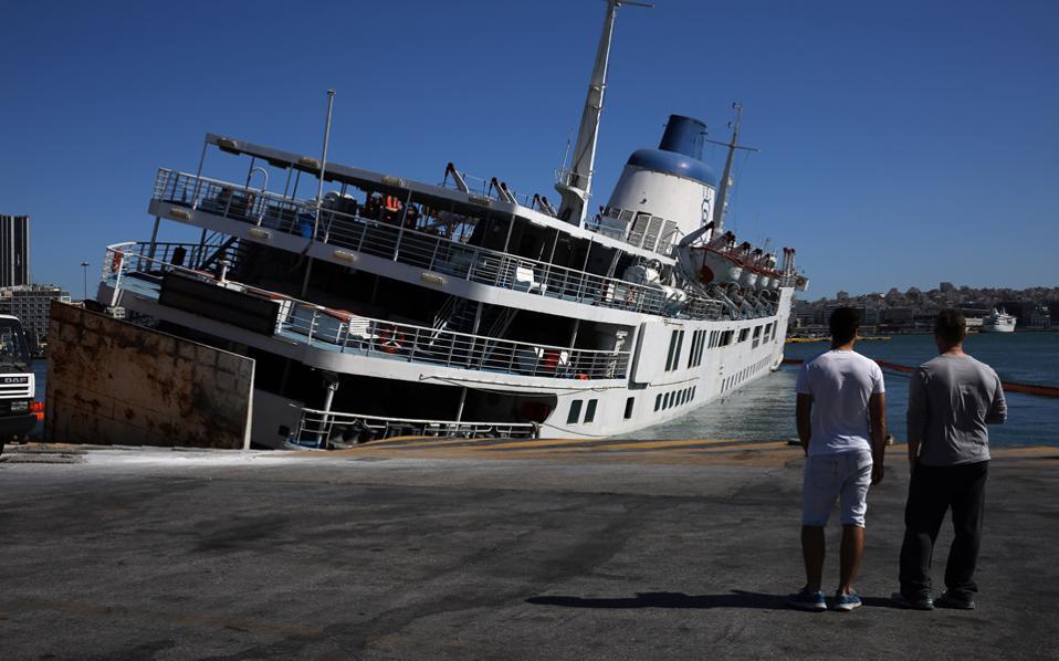 Το πλοίο παραμένει ημιβυθισμένο καταμεσής του λιμανιού, αμαυρώνοντας την εικόνα του Πειραιά.