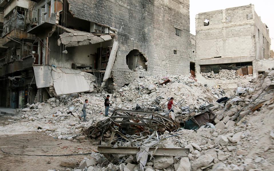 Παιδιά μετρούν το μέγεθος της καταστροφής που άφησαν πίσω τους οι καταιγιστικοί βομβαρδισμοί στη συνοικία Αλ Καλασέχ, στο ανατολικό Χαλέπι.