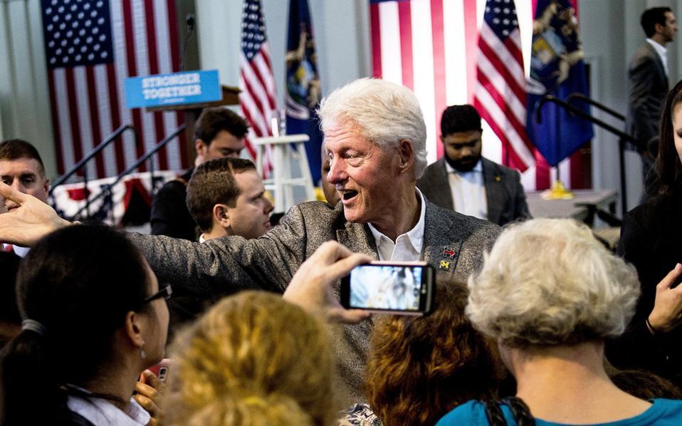 Ο πρώην Αμερικανός πρόεδρος Μπιλ Κλίντον σφίγγει χέρια οπαδών της συζύγου του Χίλαρι, μετά την ομιλία που πραγματοποίησε τη Δευτέρα στην πόλη Φλιντ του Μίσιγκαν.