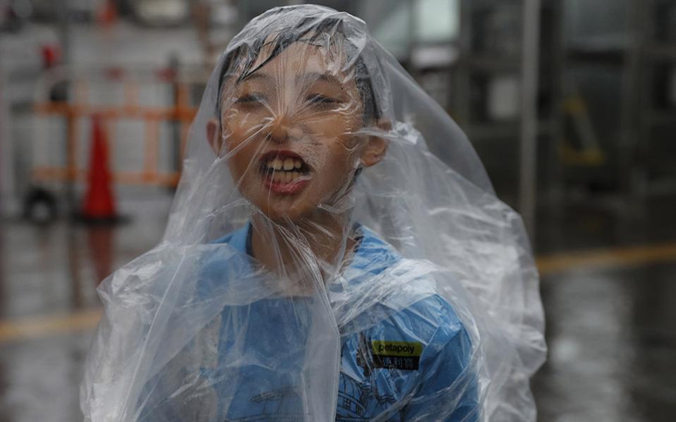 Η διασκέδαση πριν από  το χαμό. Ενα αγόρι παίζει με το αδιάβροχό του, καθώς οι θυελλώδεις άνεμοι σαρώνουν το λιμάνι Victoria στο Hong Kong. Ο τυφώνας Haima πλησιάζει την περιοχή, αφού πέρασε από τις Φιλιππίνες προκαλώντας πλημμύρες, κατολισθήσεις και διακοπές ρεύματος. (AP Photo/Vincent Yu)