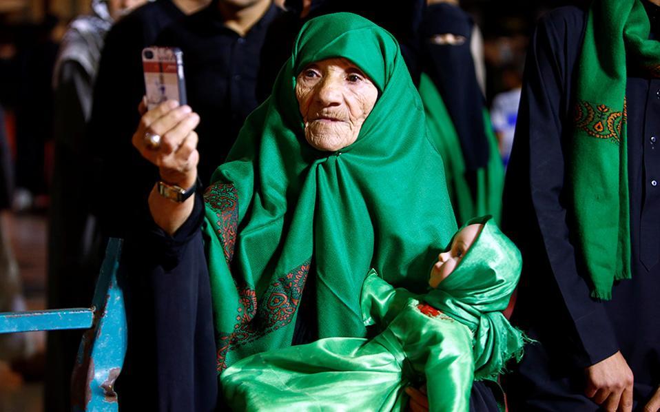 Θρησκεία, τεχνολογία, ηλικία. Με μια πλαστική κούκλα για μωρό και ντυμένη στα πράσινα, όπως ορίζει το τελετουργικό, μια πιστή συμμετέχει στους εορτασμούς της Ashura στην Najaf του Ιράκ.   Όσο για την selfie, αποτελεί τρανή απόδειξη πόσο εύκολη έχει γίνει η τεχνολογία των κινητών. REUTERS/Alaa Al-Marjani