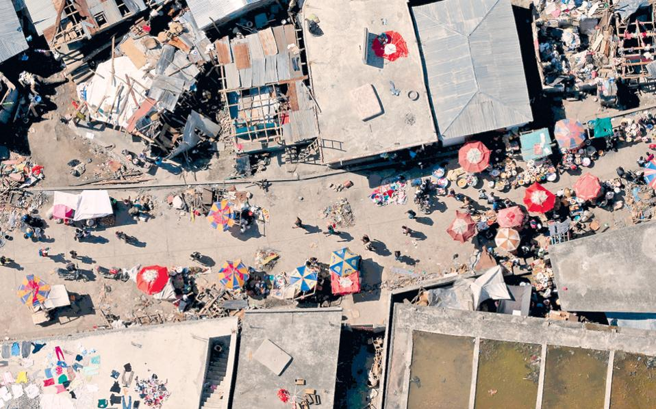 Υπαίθρια αγορά εν μέσω κατεστραμμένων σπιτιών λόγω του τυφώνα «Μάθιου» στο Τζέρεμι της Αϊτής.