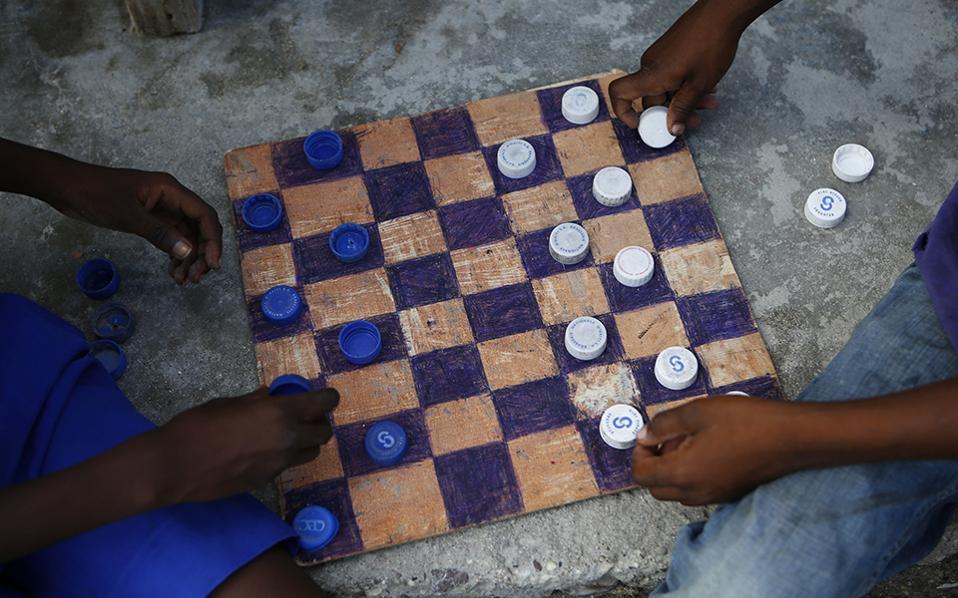 Χαρά ή λύπη; Δεν μπορεί κανείς παρά να θαυμάσει την εξυπνάδα και την εφευρετικότητα των δυο παιδιών, που με το τίποτα, έφτιαξαν ένα παιχνίδι και μάλιστα  στρατηγικής και σκέψης. Από την άλλη, τα δυο παιδιά στην Αϊτή δεν έχουν τίποτα, ούτε καν σπίτι, μετά τον τυφώνα Mattew και πώς να καταλήξεις ελαφρά τη καρδία στο συμπέρασμα, ότι αυτή η ανάγκη τους οδήγησε στην δημιουργία; (AP Photo/Rebecca Blackwell)